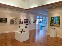 Picture: White gallery with 11 small works hanging on the wall at a distance and 5 pedestals with small sculpture resting on them in the center of the room.